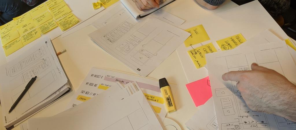 people in the workshop woking on paper mobile prototypes